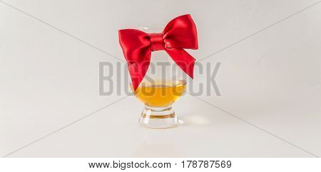 One Glass Of Exquisite Single Malt Whiskey, Red Bow, White Background