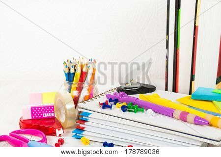Many school stationary the white wooden table with copy space