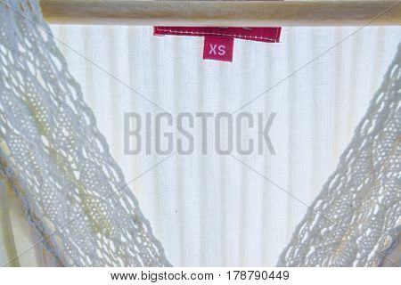 Closeup of whie linen cloth with insertion and pink size label