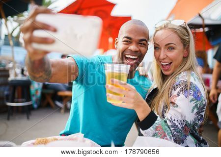happy couple taking selfie together at outdoor pub or bar