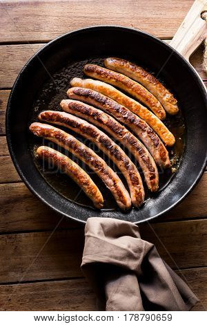 Delicious fried sausages with golden crust in iron cast pan linen towel top view minimalist