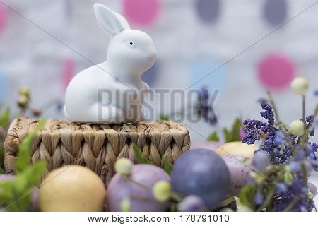 Funny Easter rabbit, colored eggs and flowers