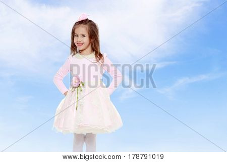 Dressy little girl long blonde hair, beautiful pink dress and a rose in her hair.She put hands on hips.On the background of summer blue sky and fluffy clouds.