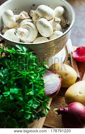 Fresh organic vegetables mushrooms potatoes onions parsley on kitchen table by window dinner ingredients top view