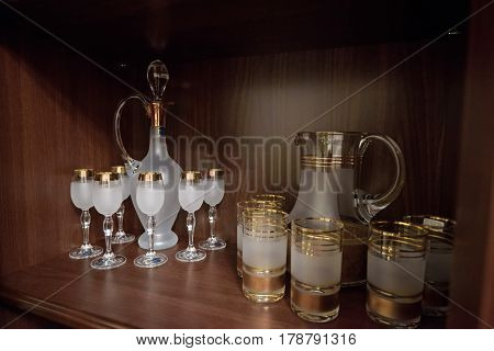 Wooden cabinet with sets of decorated crystal glasses with frosted glass