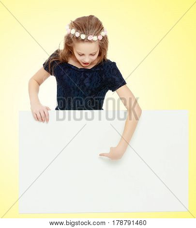 Beautiful little girl with a wreath on his head pointing at the banner.On a yellow gradient background.