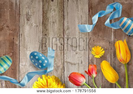 Easter decoration background with colored eggs, ribbon and flowers and copy space for message.