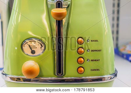 Closeup of old-fashioned green retro toaster with orange buttons