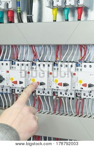 The man turns off the circuit breaker protecting the motor in an electric Cabinet or panel. Automatic switches connected by wires with marking. Top visible introductory circuit breaker.