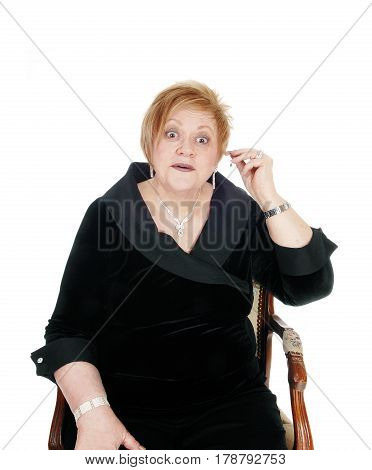 A surprised senior woman in a black dress sitting in an armchair and putting an hearing aid in her ear isolated for white background.