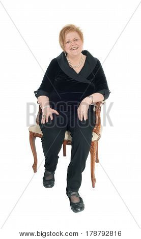 A happy smiling senior citizen woman in a black suit sitting in an old armchair relaxing isolated for white background.