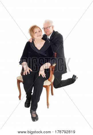 A nice senior citizen couple she sitting in an old armchair he kneeling behind her his hands on her shoulder isolated for white background.