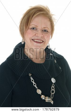 A older senior woman in a black dress and big necklace standing smiling isolated for white background.