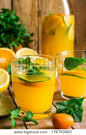 Refreshing citrus lemonade with fresh mint glasses bottle cut fruits on wood kitchen table by window sunlight