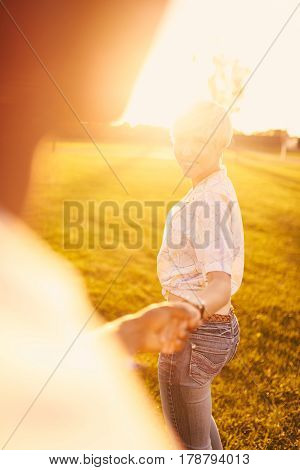 Point of view portrait of a diverse couple in love hanging out in a city parc holding hands at sunset with flare sunlight. Artistic golden sunflare serie