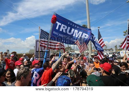 Huntington Beach, CA - March 25 2017: Make America Great Again March. Supporters and protesters of republican president Donald Trump, wave flags, and hold signs at a MAGA March in Huntington Beach.