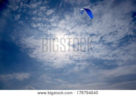 Big blue sport kite flying high in bright sky against the light