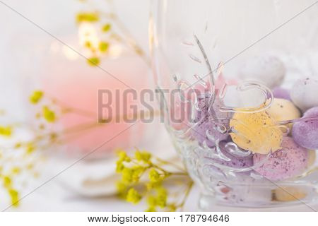 Easter table setting details chocolate eggs in elegant glass candle flowers white background styled image