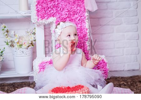 Little girl eating cake in white dress