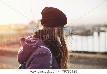 Hipster girl walking on the bridge at sunset