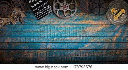 Cinema concept of vintage film reels, clapperboard and projector on old wooden background.