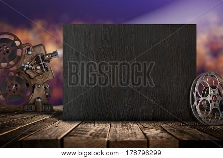 Cinema concept of vintage film reels, clapperboard and projector ond old wooden background.