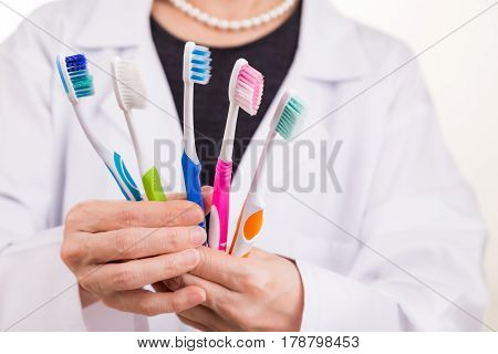 Dentist Holding Toothbrushes With Different Head And Bristle Design