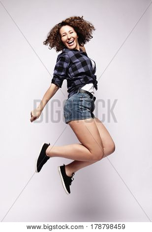 Full length portrait of a cheerful young woman jumping  on a white background