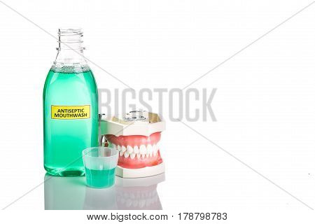 Antiseptic monthwash with dental teeth model used by dentist for education on oral care.