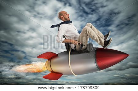 Businessman flying over a rocket in the sky. Increase the climb to success concept