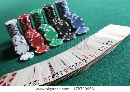 set of chips and cards on green baize gambling casino