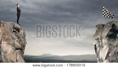 Man looks at a checkered flag on the other side of the mountain. Business concept of businessman overcome the problems.
