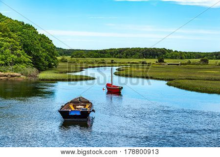 Two boats lay at anchor on the Herring River at Harwich Massachusetts on Cape Cod.