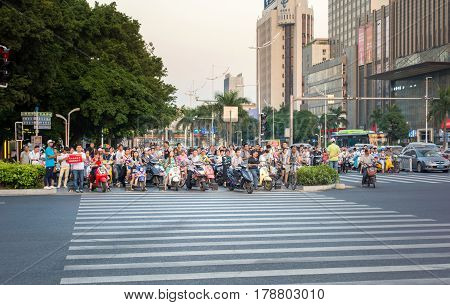 Guangzhou, China - September 19, 2016: Busy Street Of Guangzhou With People On Motorbikes