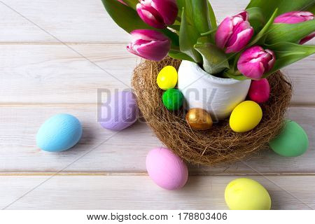 Easter Table Centerpiece With Decorated Eggs In Nest And Pink Tulips