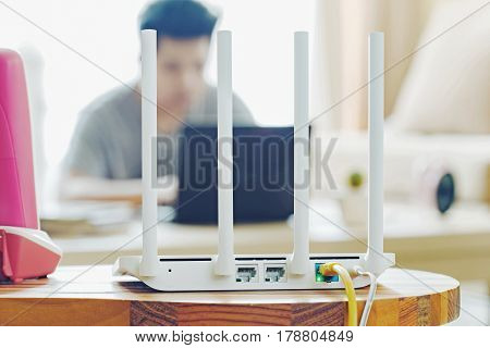 closeup of a wireless router and a man using notebook on living room at home ofiice