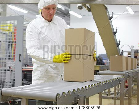 Manual worker in white uniform,cap and yellow gloves, at production line dealing with boxes