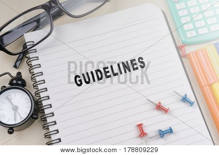 GUIDELINES words on notebook with office supplies