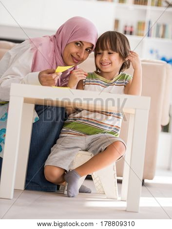 Arabic mother with little son learning in living room