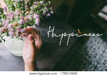 Life quote. Motivation quote on soft background. The hand touching purple flowers. Happiness.