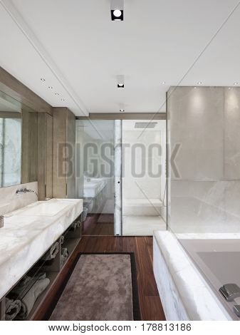 Modern bathroom with marble and parquet