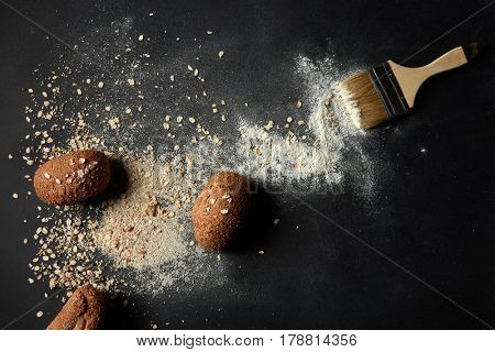 Baked buns with brush, oat flakes and flour over black background