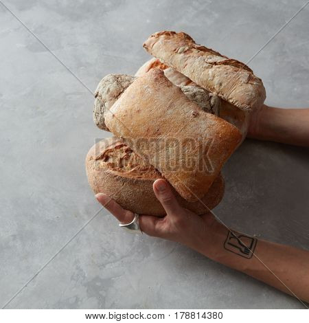 Close up view of female hands holding different types of bread