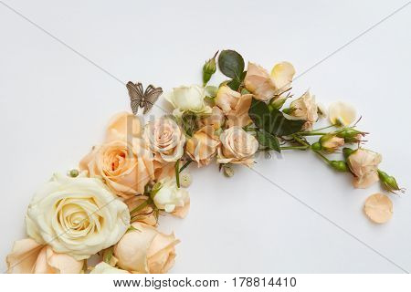 Close up of branch of orange flowers with metal butterfly over white background
