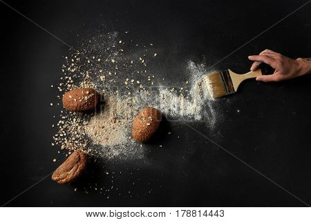 Top view of buns with oat flakes and flour, human hand holding brush over black background