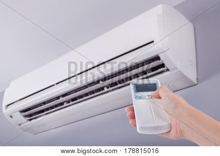 Hand Holding Remote Control Directed On Air Conditioner