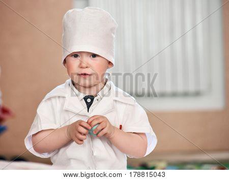 Portrait of small cute boy in white doctor uniform