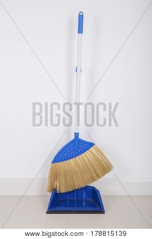 Broom And Dustpan On Floor With Wall Background