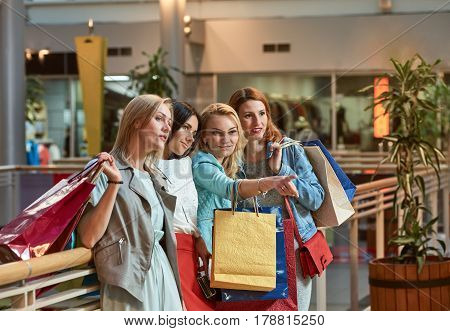 shopping girls with bags point at showcase