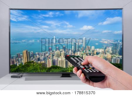 Hand holding TV remote control with a television and city screen in the background